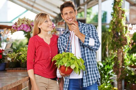 garden staff: Happy couple with a philodendron plant in a garden center