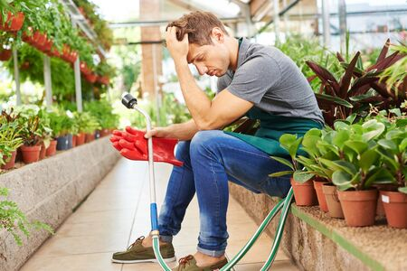garden staff: Exhausted man with burnout sitting in a nursery shop