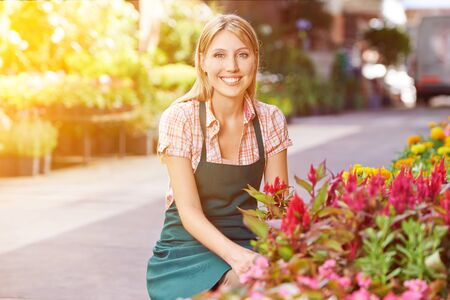 woman shop: Happy young woman as gardener in front of a flower shop Stock Photo
