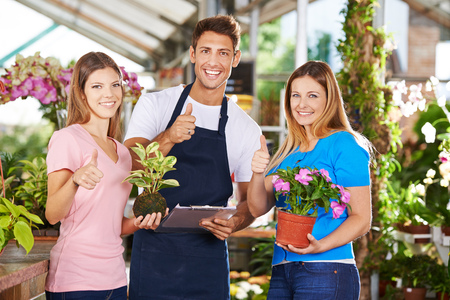 garden staff: Happy team of gardeners in a nursery shop holding thumbs up