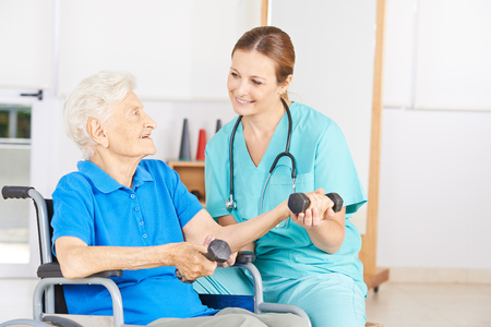 persona en silla de ruedas: Mujer mayor sonriente en el levantamiento de pesas en silla de ruedas en la fisioterapia
