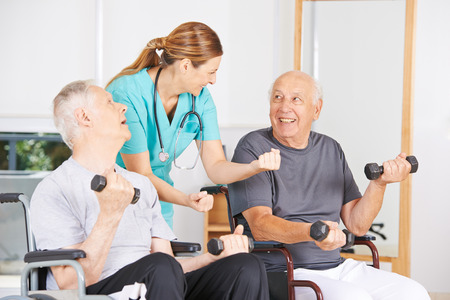Geratric nurse motivating senior men in wheelchairs in physiotherapy