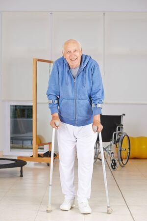 fisioterapia: Senior anciano caminando con muletas en la fisioterapia