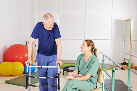 pielęgniarki: Stary człowiek z walker w fizykoterapii w domu opieki Zdjęcie Seryjne