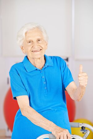 mobility nursing: Happy senior woman holding her thumbs up in a nursing home Stock Photo