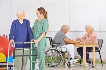 Sorridente infermiera geriatrica con un gruppo di persone anziane in una casa di cura