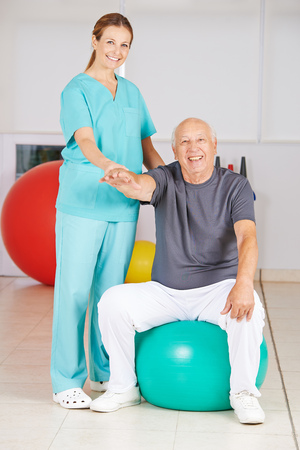 fisioterapia: Viejo hombre que hace detrás la formación en hogar de ancianos con un fisioterapeuta
