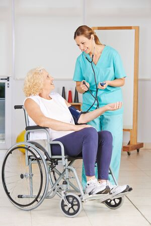 outpatient: Senior woman in wheelchair getting blood pressure measurement in a nursing home