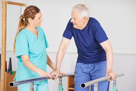 El viejo hombre que ejercita con el fisioterapeuta en una barra horizontal