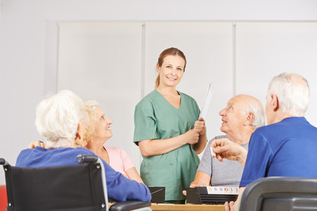 home health nurse: Smiling female geratric nurse standing with a group of senior people