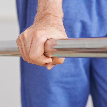 fisioterapia: Vieja mano del hombre mayor que se aferra a manejar de una cinta de correr