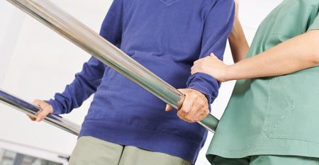 Handen van oude vrouw op de handvatten van een loopband in de fysiotherapie Stockfoto