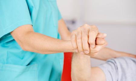 nursing: Geriatric nurse holding hands of senior man for consolation
