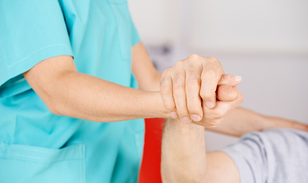 Geriatric nurse holding hands of senior man for consolation