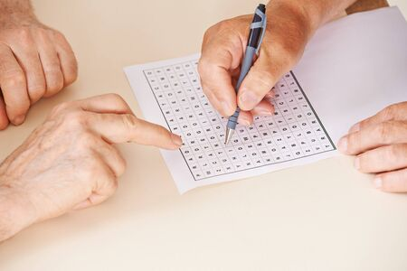 quiz: Hands of two senior people solving together a word search quiz Stock Photo