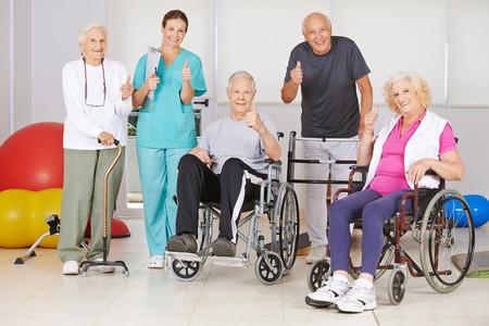 Feliz grupo de personas mayores y de enfermería que detienen los pulgares en fisioterapia