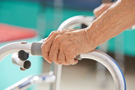 Oude hogere handen vast te houden aan een rollator om steun Stockfoto