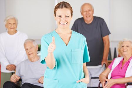 Gelukkig verpleegkundige assistent houdt haar duimen omhoog voor een gelukkige groep van hooggeplaatste personen
