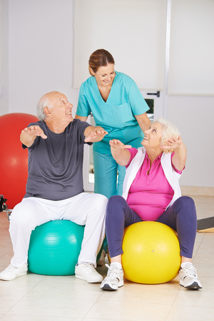 physiotherapy: Two senior people doing fitness training in physiotherapy with physiotherapist