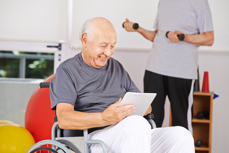 old age home: Disabled old man sitting in wheelchair with tablet PC in a nursing home