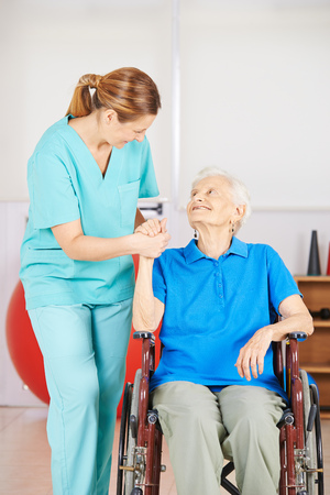 terapia ocupacional: Cuidador femenina que sostiene la mano de una anciana en silla de ruedas