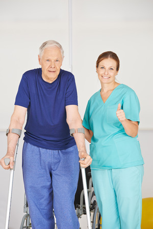elderly woman: Physiotherapist holding thumbs up next to senior man with crutches Stock Photo