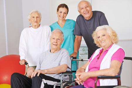 Lächelnde Gruppe ältere Leute mit Physiotherapeut in einem Pflegeheim