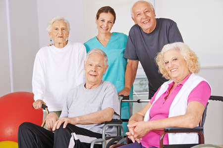age old: Smiling group of senior people with physiotherapist in a nursing home