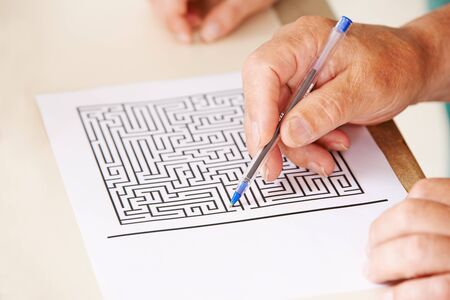 eldercare: Hand of senior man with pen doing memory training with a paper maze