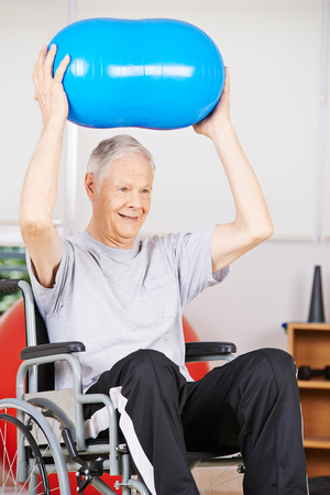 gym ball: Old man in wheelchair in psychotherapy lifting a gym ball