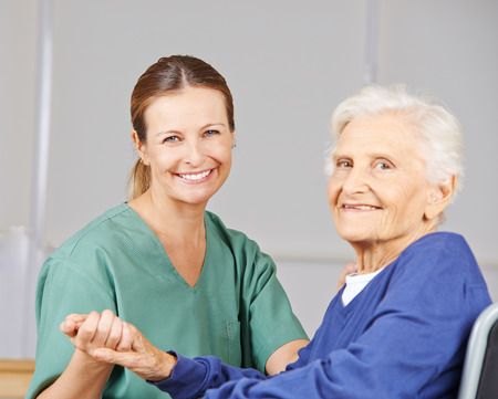 nursing care insurance: Old smiling senior woman with geriatric nurse in a nursing home Stock Photo