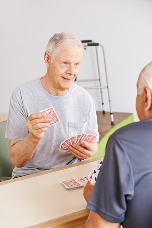 skat: Two senior people playing cards in a nursing home