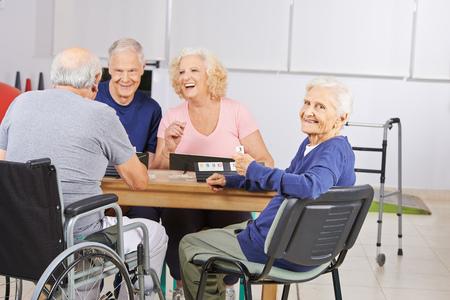 Mulher adulta na casa de repouso de jogo com rindo pessoas seniores