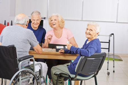 old people group: Old woman in nursing home playing with laughing senior people