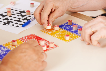 damas antiguas: Manos de las personas mayores jugando bingo juntos en un hogar de ancianos