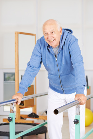 old man standing: Old man standing on high bar in physiotherapy