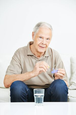 eldercare: Senior man taking pills out of medicine container at home Stock Photo