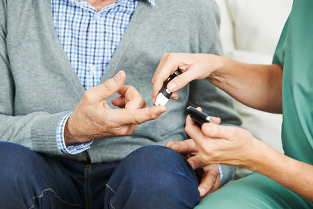 Blood glucose monitoring on finger of senior man with diabetes Stock Photo - 46991940