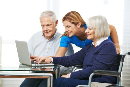 an elderly person: Mujer sonriente ayudar a pareja de ancianos con el ordenador port�til y el Internet