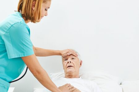 geriatric nurse: Old man with fever in bed with nurse touching his forehead