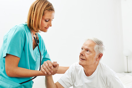 house call: Nurse in nursing home helping senior man getting up from bed Stock Photo