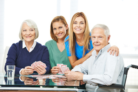 retirement homes: Group of senior people playing cards in nursing home with geriatric nurse Stock Photo