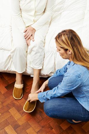 Geriatrische Pflegekraft, die älterer Frau hilft, die auf Pantoffeln sich setzt