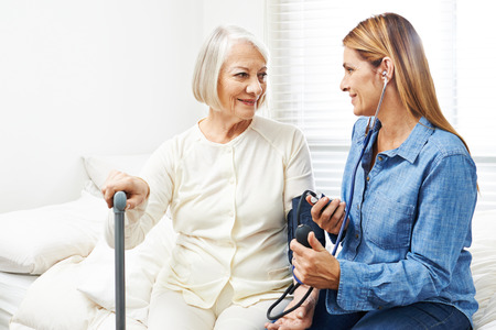Caregiver doing blood pressure monitoring for senior woman at home Stock Photo