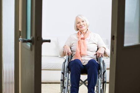 persona en silla de ruedas: Anciana sentada en una silla de ruedas en el hogar