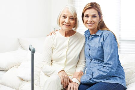 house call: Happy senior woman with adult daughter sitting at home on a bed Stock Photo