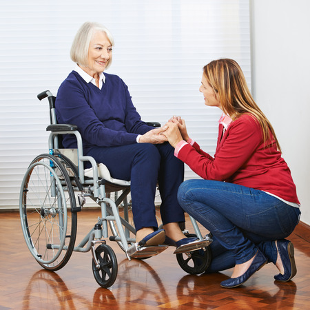 social work aged care: Smiling senior woman in wheelchair with adult daughter holding hands Stock Photo