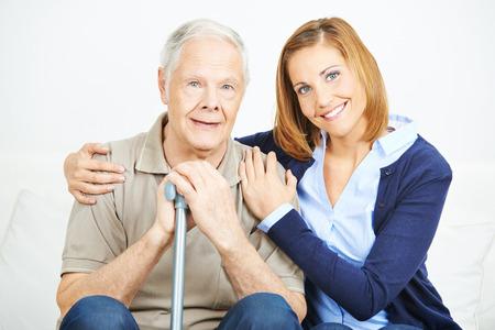 nurses: Mujer sonriente con el hombre mayor en un hogar de ancianos Foto de archivo