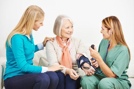 Enkelin und ältere Frau mit Krankenschwester tut Blutdruckmessung Lizenzfreie Bilder