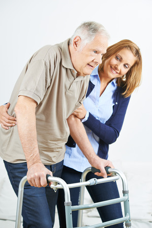 crutches: Physiotherapist helping old senior man in rehab
